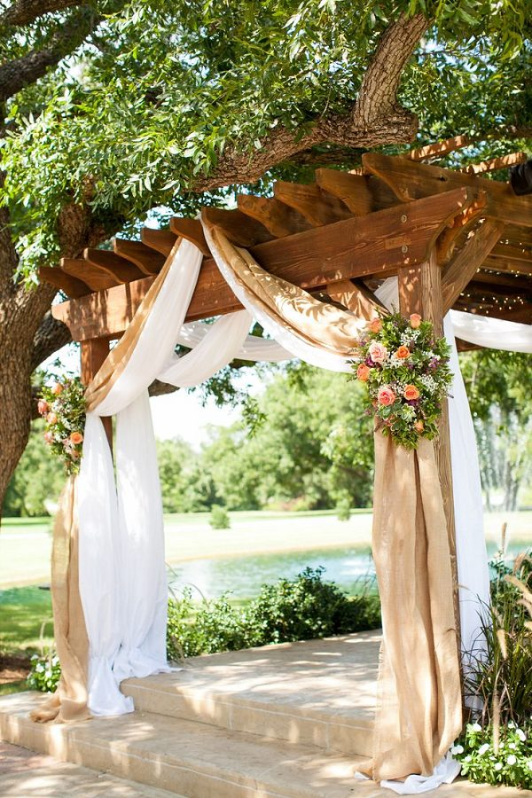 rustic-Burlap-draping-with-country-pink-and-green-flowers-over-a-wooden-pergola